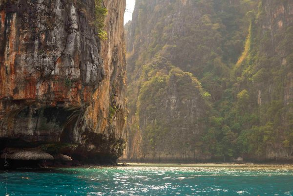 A kayaker beneath Phi Phi's majestic cliffs.