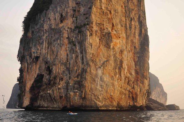 A kayaker beneath Phi Phi's majestic cliffs.